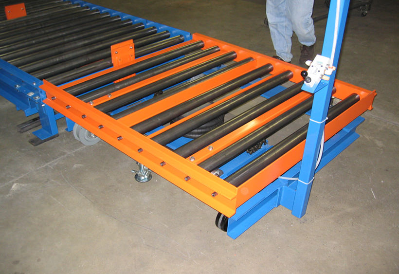 Manual transfer car with gravity conveyor and air bag tilter