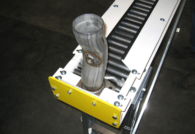 Gravity roller conveyor for exhaust fitting