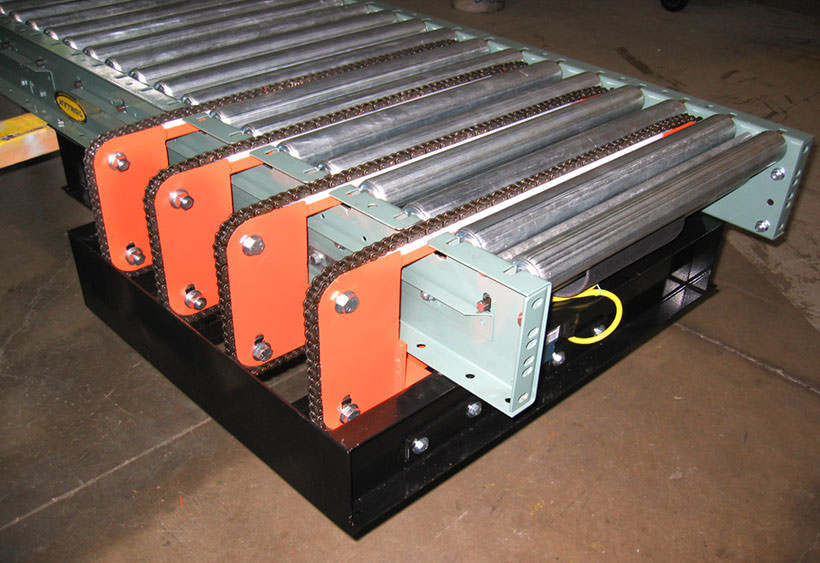 Small four strand chain transfer mounted in belt driven roller conveyor